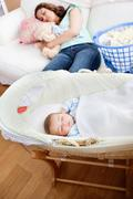 Young mother sleeping on the sofa while her baby is sleeping in his cradle in Stock Photos
