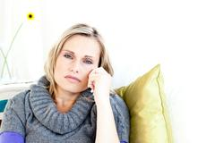 portrait of a depressed woman lying on a sofa - stock photo
