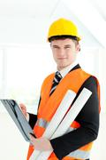 self-assured archticet holding a clipboard and blueprints - stock photo