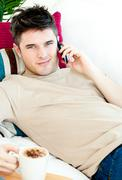 Handsome young man talking on phone at home Stock Photos