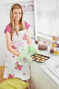 positive young woman baking cookies in the kitchen - stock photo