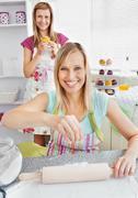 animated female friends baking muffins smiling at the camera - stock photo