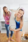 enthusiastic women holding a carpet standing in the kitchen - stock photo