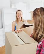 Stock Photo of two radiant female friends holding boxes after moving