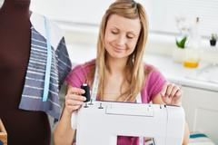 Stock Photo of bright young woman using her sewing machine