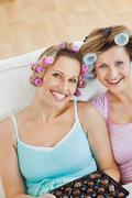 Delighted women wearing hair rollers eating chocolate looking at the camera Stock Photos