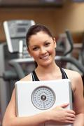 Cute woman holding a scales and smiling at the camera Stock Photos