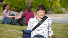 Positive male student lying on the grass with his schoolbag Stock Photos