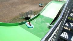 People enjoying on water slide at aqua park Stock Footage
