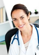 self-assured female doctor smiling at the camera - stock photo