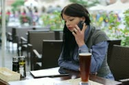 Attractive businesswoman talking on cellphone in the cafe NTSC Stock Footage