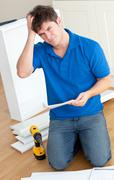 incomprehensive caucasian man reading the instructions to assemble furniture  - stock photo