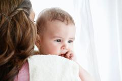 Portrait of a mother pampering her baby after the bath at home Stock Photos