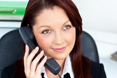 Assertive young businesswoman talking on phone smiling at the camera Stock Photos