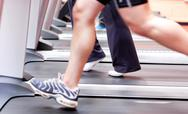 Close-up of the legs of an athletic young woman exercising on a running machi Stock Photos