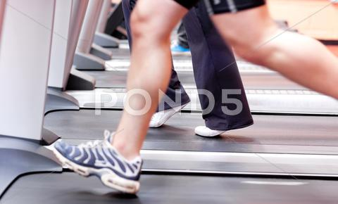 Stock photo of close-up of the legs of an athletic young woman exercising on a running machi