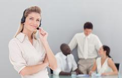 self-assured female sales respresentative with her team - stock photo