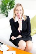 self-assured businesswoman smiling at the camera sitting on the sofa - stock photo