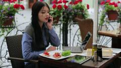 Businesswoman with laptop receiving phone call during lunch in cafe HD Stock Footage