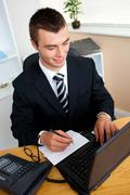 animated young businessman using his laptop writing on a paper - stock photo
