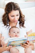 Attentive mother reading a book to her adorable baby sitting in the couch Stock Photos