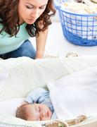 attentive mother keeping an eye on her baby sleeping in his cradle - stock photo