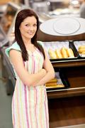 self-assured female cook smiling at the camera in front of her bakery - stock photo