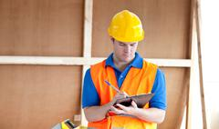 Self-assured male worker writing on a clipboard Stock Photos