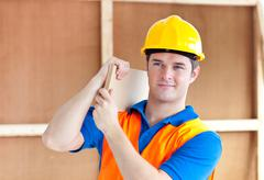 assertive young male worker with a yellow helmet carrying a wooden board - stock photo