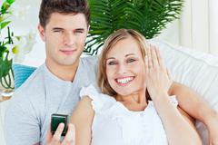 blissful woman showing her wedding ring to the camera lying with her boyfrien - stock photo