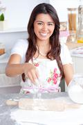 Captivating asian woman baking in her kitchen Stock Photos