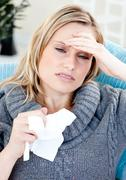 caucasian woman with headache and tissues at home - stock photo