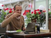Stock Video Footage of Young man with modern laptop eating lunch in cafe NTSC
