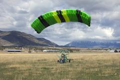 Pilot landing ultralight power parachute in field Stock Photos