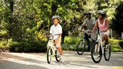 Healthy diverse family outdoors together riding   - stock footage