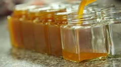 Poring marmalade in jar Stock Footage
