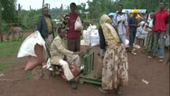 Stock Video Footage of African coffee market woman load scale with harvest sack, man measures WS