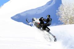 Snowmobile climbs steep mountain cliff in winter Stock Photos