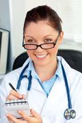 self-assured female doctor smiling at the camera holding a notepad - stock photo