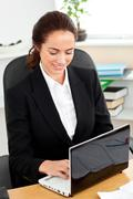 Stock Photo of assertive businesswoman looking at the camera sitting in her office