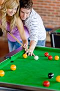 affectionate boyfriend learning his girlfriend how to play pool - stock photo
