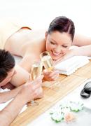 loving young couple drinking champagne lying on a massage table - stock photo