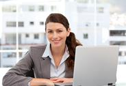 Stock Photo of smiling woman on the computer looking at the camera