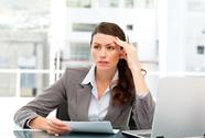 Serious female executive finding ideas while working at her desk Stock Photos