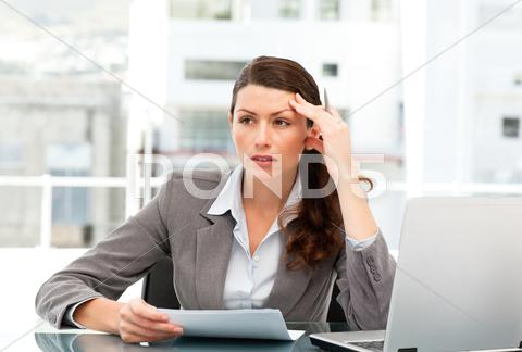 Stock photo of serious female executive finding ideas while working at her desk
