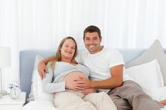 Attentive man touching the belly of his wife Stock Photos