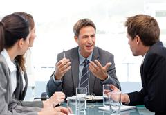 Stock Photo of charismatic chairman talking with his team