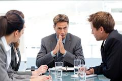 Serious manager talking to his team during a meeting Stock Photos