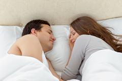 Serene couple sleeping together on their bed Stock Photos