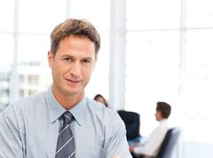 severe businessman standing in front of his team while working at a table - stock photo